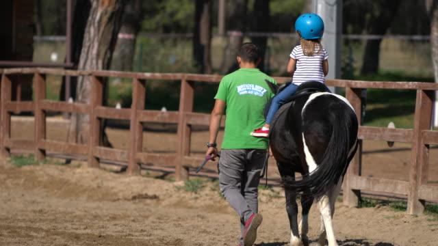 vídeos de stock, filmes e b-roll de garota feliz tendo uma aula de equitação - montar um animal