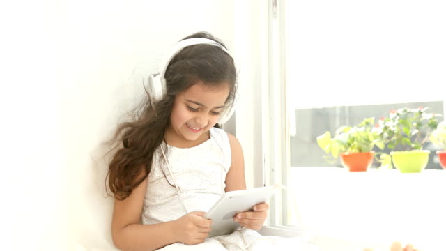 ms pan happy girl using digital tablet for listening music on headphones while sitting on window sill at home / delhi, india - one girl only stock videos & royalty-free footage