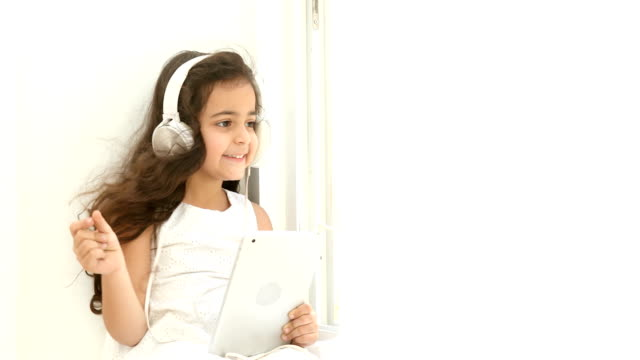 ms happy girl using digital tablet for listening music on headphones while sitting on window sill at home / delhi, india - snapping stock videos & royalty-free footage