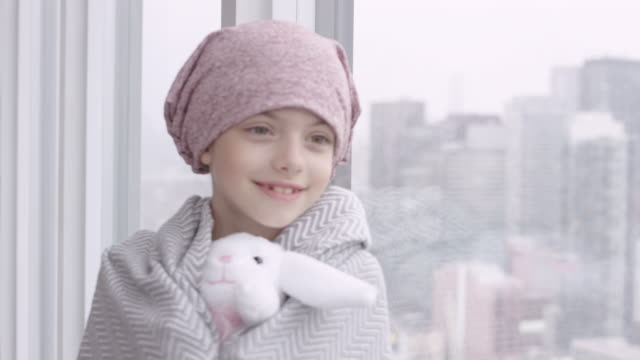 happy girl with cancer leaning against window - headscarf stock videos & royalty-free footage