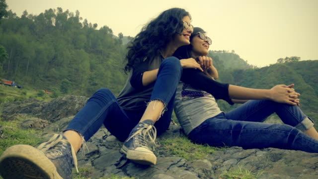 Chica feliz con su amiga disfrutando de vacaciones en colinas.