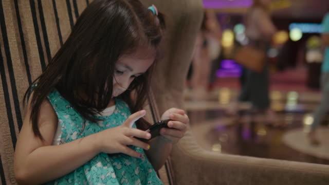 vídeos y material grabado en eventos de stock de niña feliz con teléfono inteligente - nativo digital