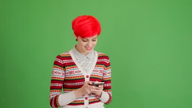 happy girl writing a message on a smartphone on a green background - blouse stock videos & royalty-free footage