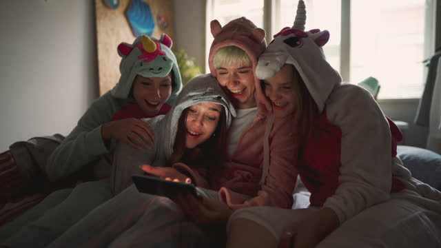 happy girlfriends at a sleepover having fun while checking social media on the smart phone. - slumber party stock videos & royalty-free footage