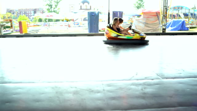 happy girlfriends driving a bumper car and smiling - bumper car stock videos & royalty-free footage