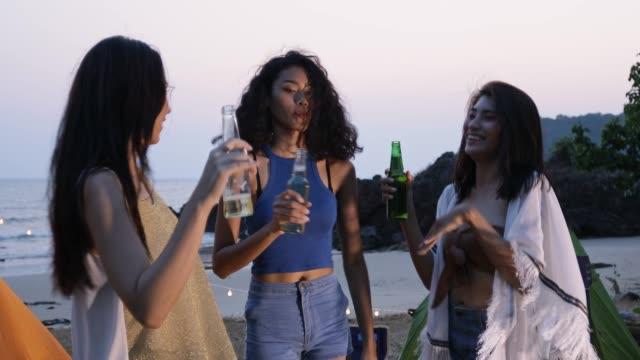幸せなガールフレンドの女性グループは、ビーチでビールを飲みます, 若い女性の友人との友情の概念時間を楽しんで、キャンプで本物の楽しみを持っています - アウトドア点の映像素材/bロール