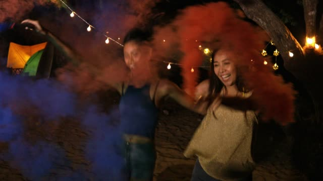 happy girlfriends women group playing color smoke at beach, friendship concept with young female friends enjoying time and having genuine fun at camping. - tenda da campeggio video stock e b–roll