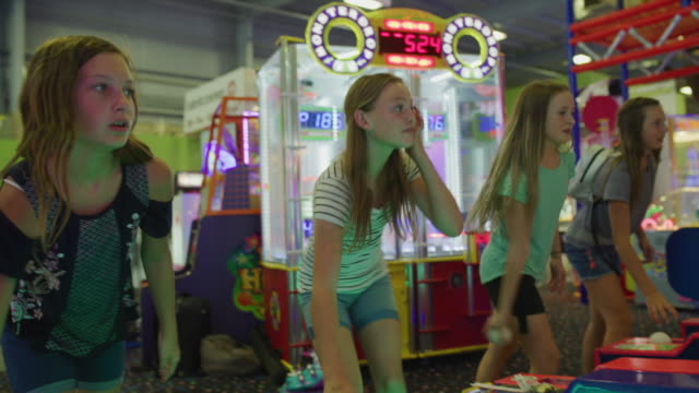 stockvideo's en b-roll-footage met happy girls playing skee ball in arcade / orem, utah, united states - driekwartlengte
