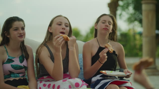happy girls sitting poolside laughing and eating pizza / cedar hills, utah, united states - stabilimento sportivo video stock e b–roll