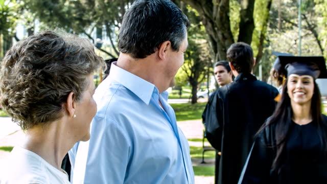 happy graduation woman hugging her proud parents - graduation stock videos & royalty-free footage