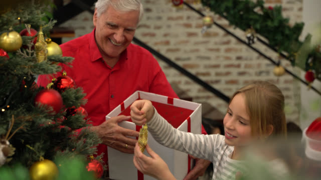 happy grandfather decorating the christmas tree with beautiful sweet girl at home - grandchild stock videos & royalty-free footage