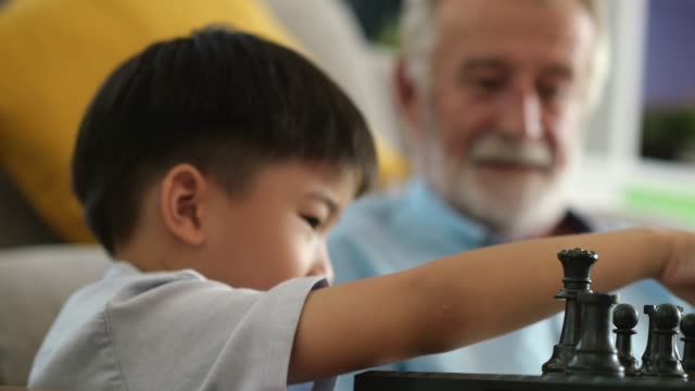 happy grandfather having a great time with his grandson - chess stock videos & royalty-free footage