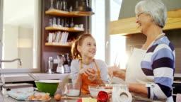 Happy grandma mixing mixture little girl standing besides her 4K 4k