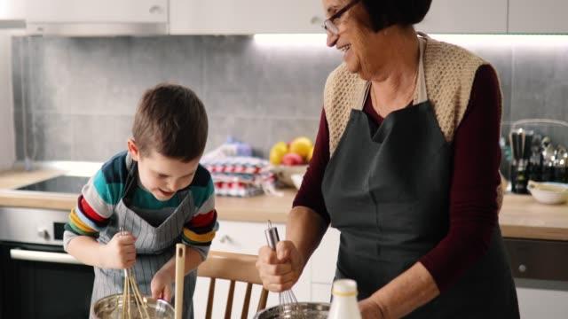 vídeos de stock, filmes e b-roll de avó e neto felizes que preparam bolinhos - avó