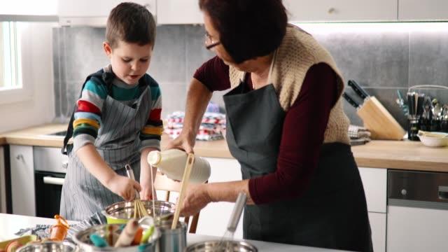 happy grandmother and grandson preparing cookies - eyewear stock videos & royalty-free footage