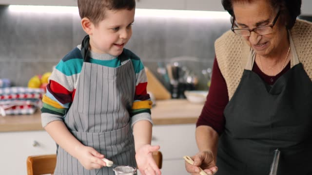happy grandmother and grandson preparing cookies - grandchild stock videos & royalty-free footage