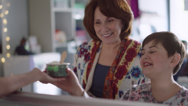 a happy grandmother and her granddaughter pay for ice cream on a tablet - credit card purchase stock videos & royalty-free footage