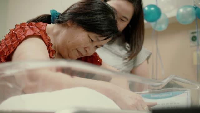 happy grandparents looking her newborn grandchild(0-1 months) in hospital nursery - 0 1 months stock videos & royalty-free footage