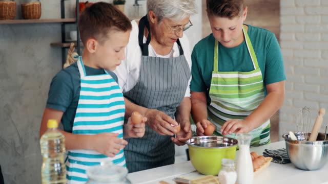 happy grandsons helping grandmother to prepare cookies - grandmother stock videos & royalty-free footage