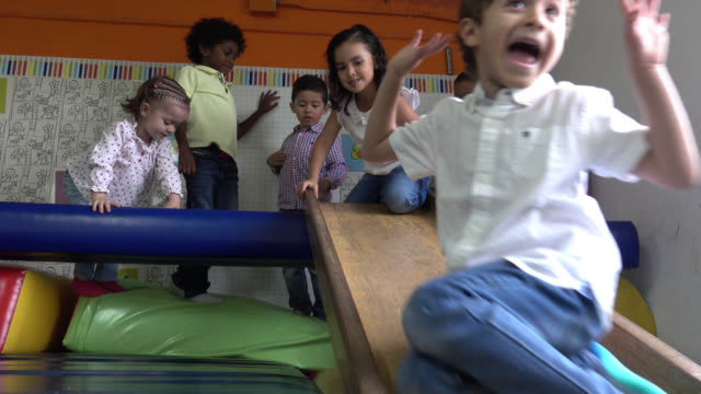 happy group of children using the children's slider - preschool stock videos & royalty-free footage