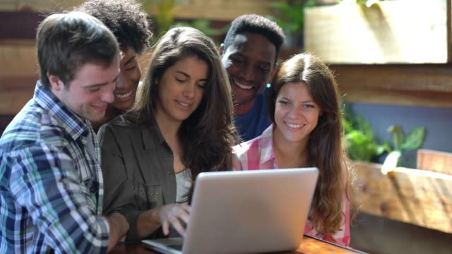 Happy group of college friends studying looking at a laptop while beautiful woman explains very friendly
