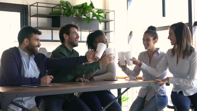 happy group of diverse colleagues toasting with take out coffee at the office celebrating and smiling - coffee variation stock videos & royalty-free footage