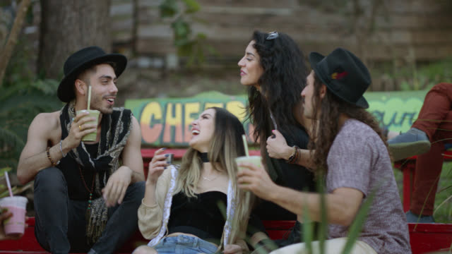 stockvideo's en b-roll-footage met happy group of diverse millennial hipsters laugh and enjoy smoothies together on a bench outside of a city cafe - smoothie