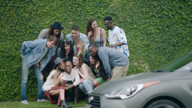happy group of diverse millennial hipsters take a group selfie in front of an ivy covered wall on the sidewalk of a busy city street - leisure activity stock videos & royalty-free footage