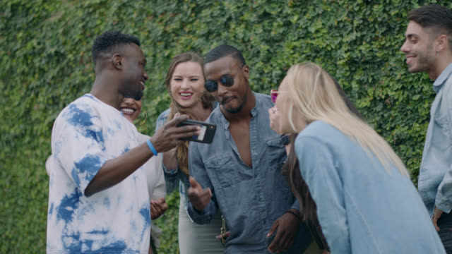 happy group of diverse millennial hipsters take a group selfie in front of an ivy covered wall on the sidewalk of a busy city street - beatnik stock videos & royalty-free footage
