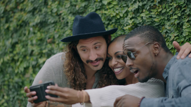 happy group of diverse millennial hipsters take a group selfie making silly faces in front of an ivy covered wall on the sidewalk of a busy city street - beatnik stock videos & royalty-free footage