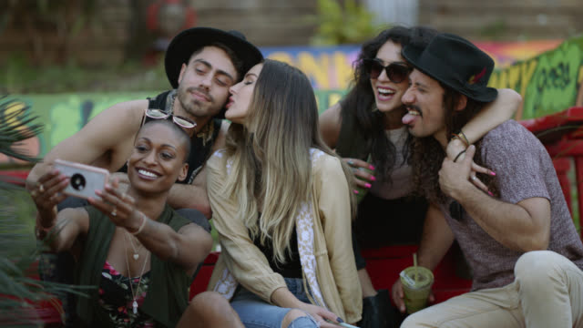 happy group of diverse millennial hipsters take a group selfie sitting on a bench outside of a city cafe - beatnik stock videos & royalty-free footage