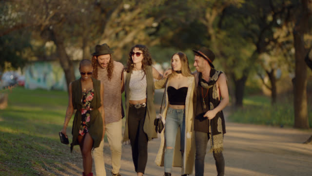 slo mo. happy group of diverse millennial hipsters wearing boho clothing walk down a deserted country dirt road - boho stock videos & royalty-free footage
