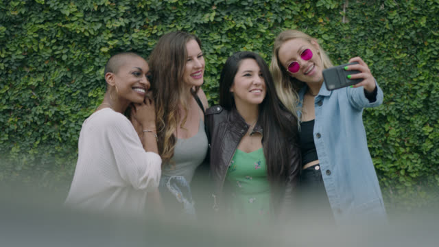 happy group of diverse millennial hipsters women take a group selfie in front of an ivy covered wall on the sidewalk of a busy city street - female friendship stock videos & royalty-free footage