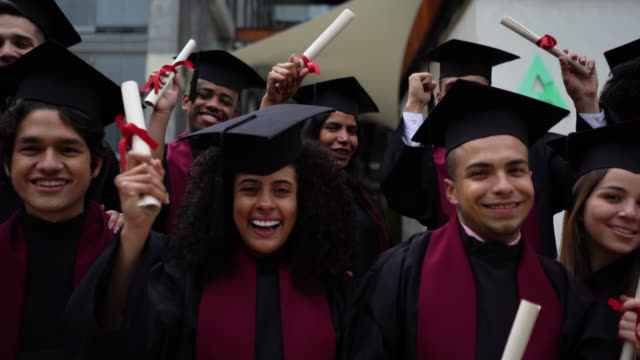happy group of diverse students holding their college diplomas facing camera with a toothy smile - diploma stock videos & royalty-free footage