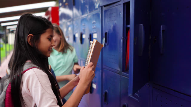 happy group of female friends at school grabbing something from locker and walking to class - locker stock videos & royalty-free footage
