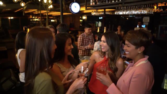 Happy group of female friends having fun at a bar gossiping and drinking cocktails