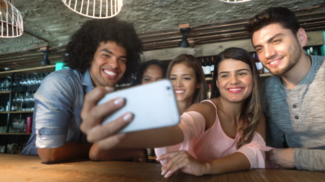 Happy group of friends at a bar taking a selfie with a smartphone smiling