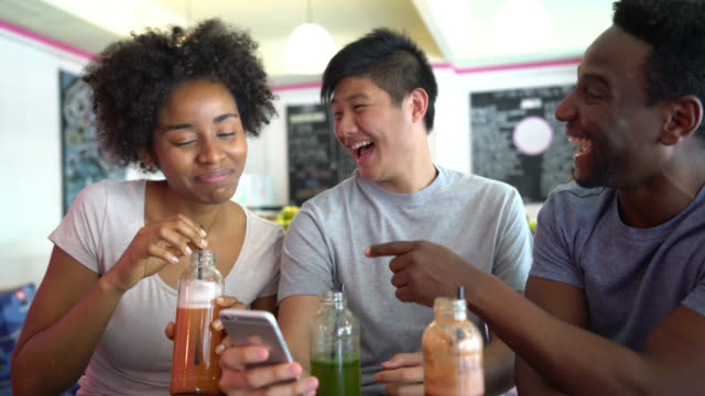 Happy group of friends at a juice bar looking at photos on a smartphone