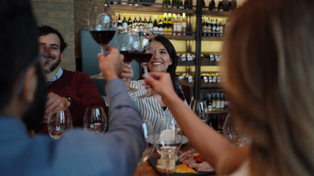 happy group of friends at a restaurant drinking wine and toasting - wine bar stock videos & royalty-free footage