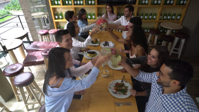 Happy group of friends at a restaurant making a toast