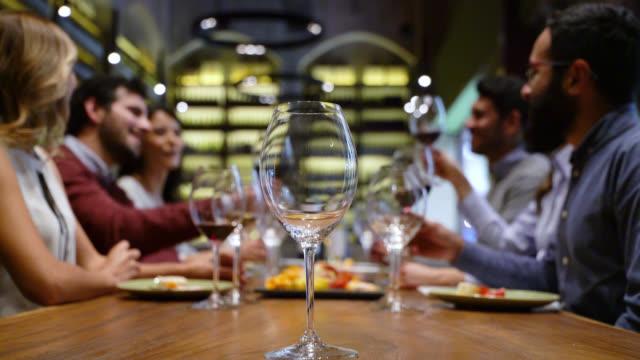 vidéos et rushes de groupe heureux d'amis à un toasting de dégustation de vin, parlant et ayant l'amusement - goûter