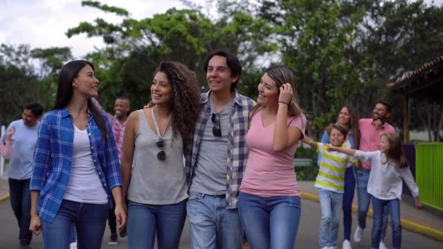 vidéos et rushes de heureux entre amis embrassant mutuellement en marchant autour d'un parc d'attractions - fête foraine