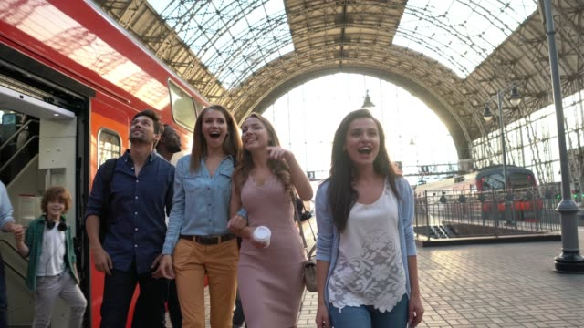 happy group of friends getting down form the train ready to do some tourism pointing and smiling - commuter stock videos & royalty-free footage