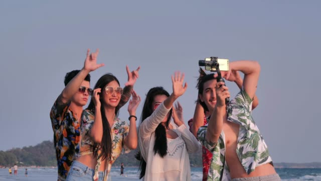 vídeos de stock e filmes b-roll de happy group of friends having fun taking a picture together on the beach.summer joy concept and multi ethnic friendship.vacations - istock - imagem
