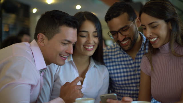 Happy group of friends looking at social media on smartphone laughing