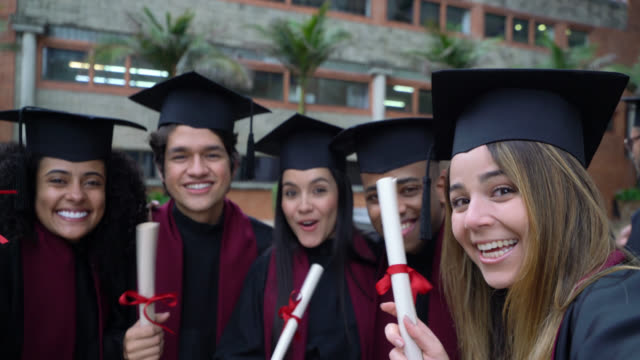 happy group of friends on a video call with someone after their graduation ceremony from college - diploma stock videos & royalty-free footage