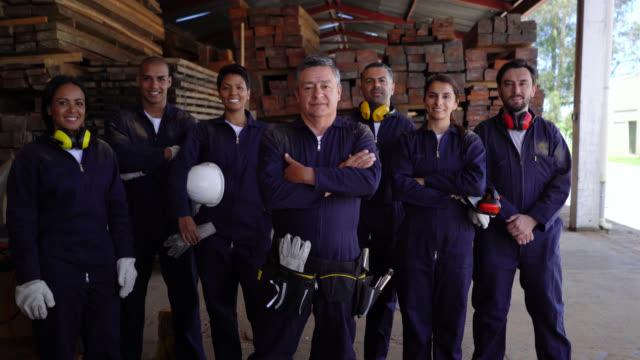 stockvideo's en b-roll-footage met gelukkige groep van latijns-amerikaanse arbeiders werken in een houtfabriek kijken naar camera glimlachend en manager het oversteken van zijn armen - vakbond