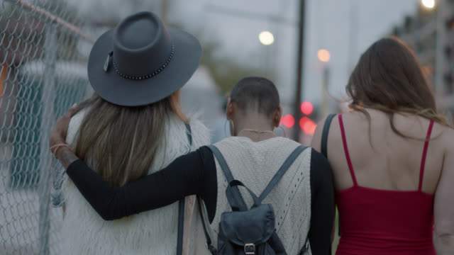 slo mo. happy group of millennial hipster women walk down a busy city street and embrace each other while they walk - hippie stock-videos und b-roll-filmmaterial