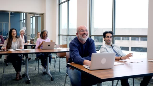happy group of mixed age, multi-ethnic college students attending class - aula video stock e b–roll