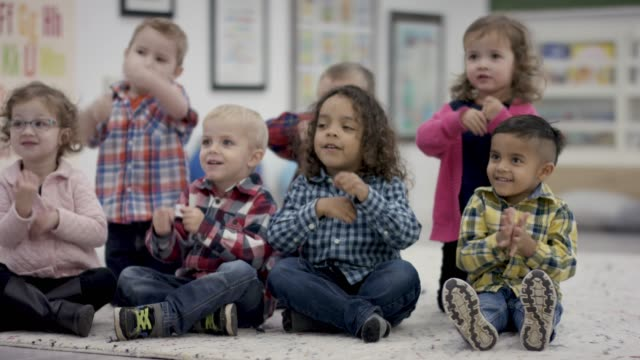 happy group of pre-school students sitting in class - preschool stock videos and b-roll footage